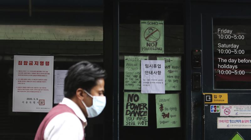 A man waring a face mask passes by notices at the entrance of a temporary closed dance club in Seoul, South Korea. (AP)
