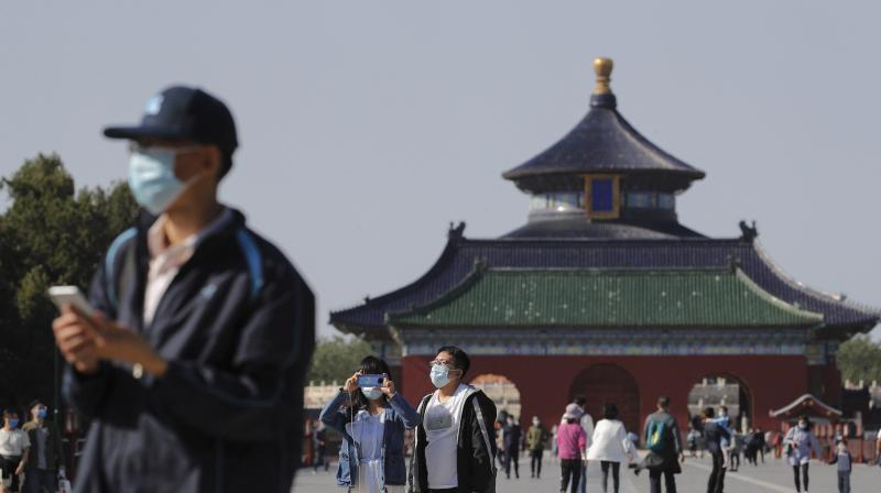 Visitors wearing protective face masks at the capital's popular tourist spot of Temple of Heaven in Beijing. (AP)