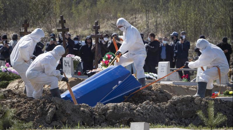 Grave diggers wearing protective suits bury a COVID-19 victim as relatives and friends stand at a safe distance in Kolpino, outside St.Petersburg, Russia. (AP)
