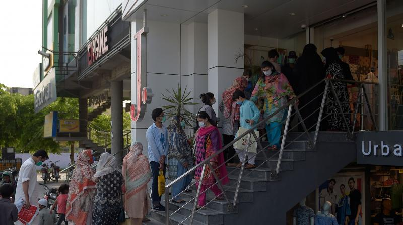 People wait for their turn outside a shop at a market after the government eased the lockdown in Islamabad. (AFP)