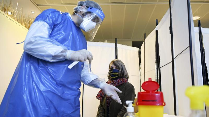 A medical staff member prepares to collect samples from a woman at a COVID-19 testing centre set up in the European Parliament in Strasbourg, eastern France. (AFP)