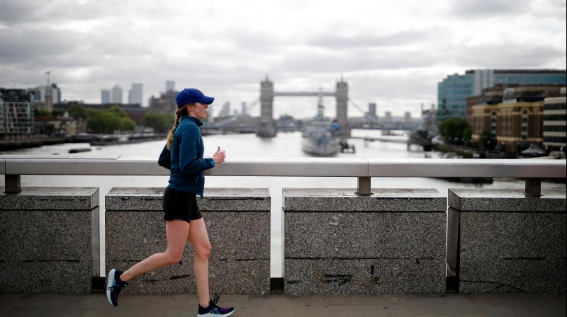 A woman runs across London Bridge, backdropped by Tower Bridge, as she exercises in central London. (AFP)