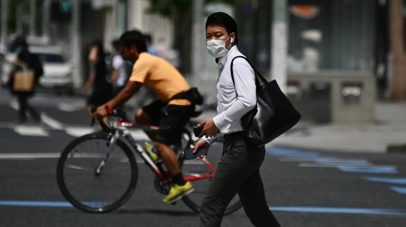 A man wearing a face mask amid the COVID-19 coronavirus outbreak walks across a street in Tokyo. (AFP)