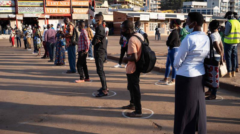 People stand in white circles drawn on the ground to adhere to social distancing measures to curb the spread of the COVID-19 coronavirus as they wait for a bus at Nyabugogo bus station in Kigali, Rwanda. (AFP)