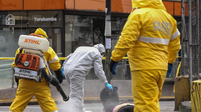 An Ecuadorian criminalistics police member disinfects the death body of a woman in a street of Quito. (AFP)