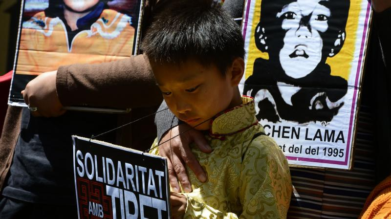 Pro-Tibetan protestors hold picures of Gendun Cheokyi Nyima (The Panchen Lama) during a demonstration outside the Chinese consulate in Barcelona. (AFP)