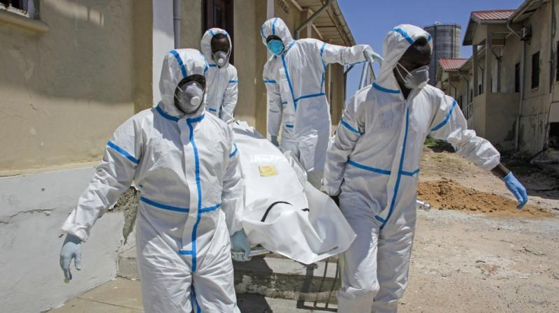 Medical workers in protective suits carry the body of Ibrahim Hassan, 56, before he is buried in Mogadishu, Somalia.(AP)