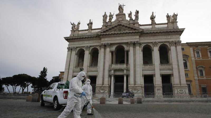 A worker in protective gear sanitizes the exterior of Saint John in Lateran Basilica, in Rome. (AP)