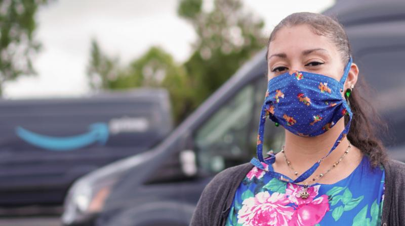 Adrienne Williams poses wearing a mask in the parking lot where she picks up her delivery van every day in Richmond, California. She delivers for Amazon, but Adrienne Williams says the e-commerce and tech giant did not deliver for her. (AFP)