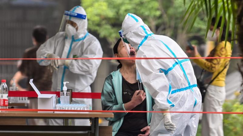 A medical worker takes a swab sample from a man to be tested for the COVID-19 novel coronavirus in a neighborhood in Wuhan. (AFP)
