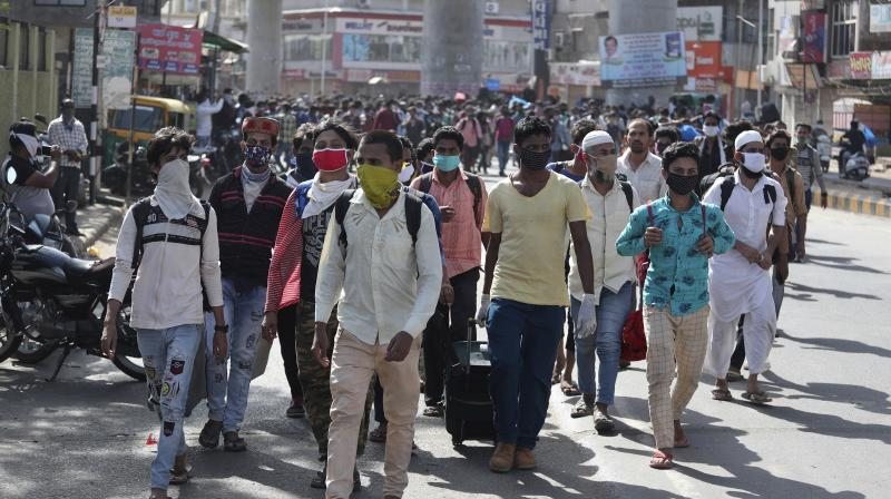 Migrant workers from other states trying to return to their homes arrives for transportation to a train station in Ahmedabad. (AP)