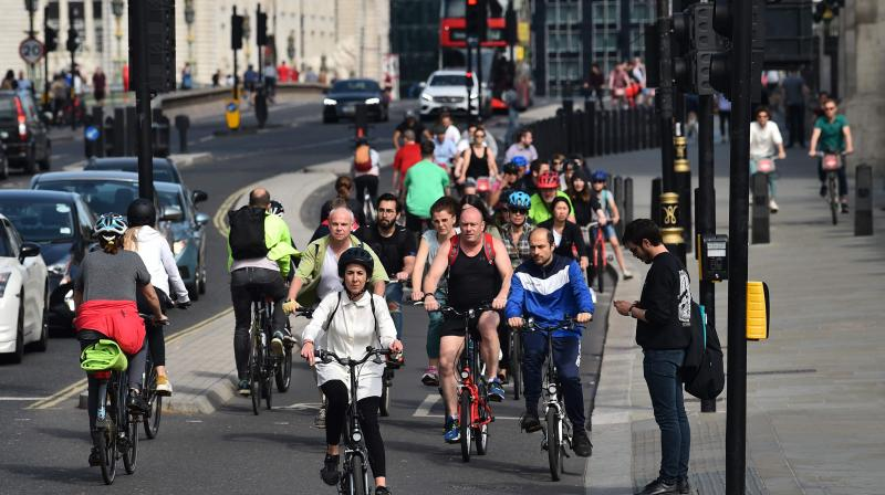People cycle through Parliament Square in central London on May 17, 2020, following an easing of lockdown rules in England. (AFP)
