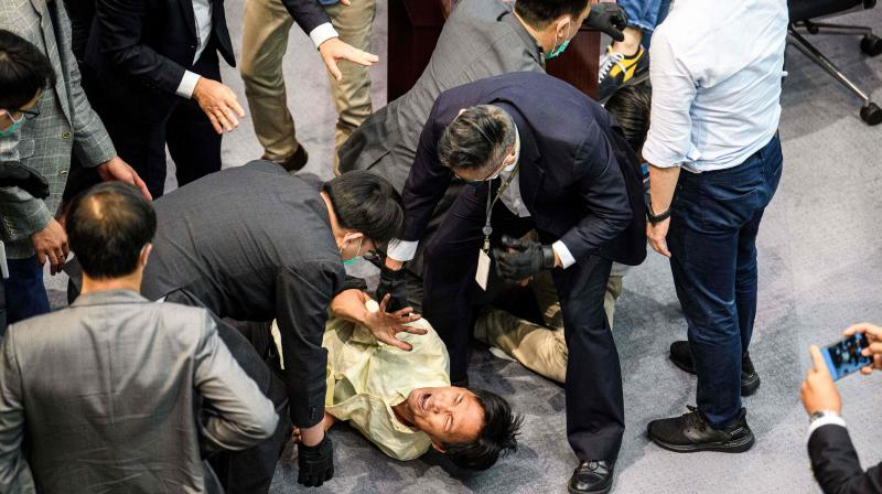 Pro-democracy lawmaker Eddie Chu (bottom C) is surrounded by security as he and other pro-democracy lawmakers scuffle with pro-Beijing lawmakers at the House Committeess election of chairpersons. (AFP)