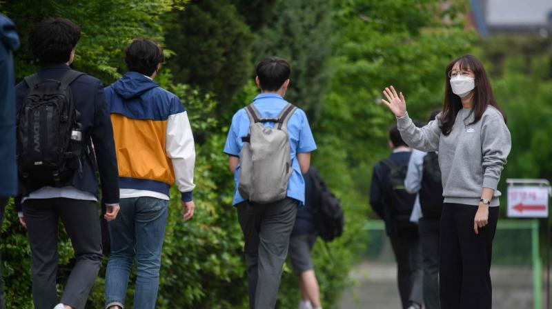 A staff member (Right) greets students as they arrive at Kyungbock High School in Seoul on May 20, 2020. (AFP)