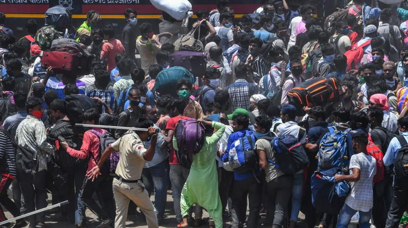 A policeman disperses guest workers gathered outside Mumbai railway station. (AFP)