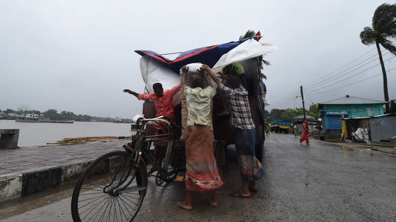 Workers unload goods from a truck ahead of the expected landfall of cyclone Amphan, in Khulna. (AFP)