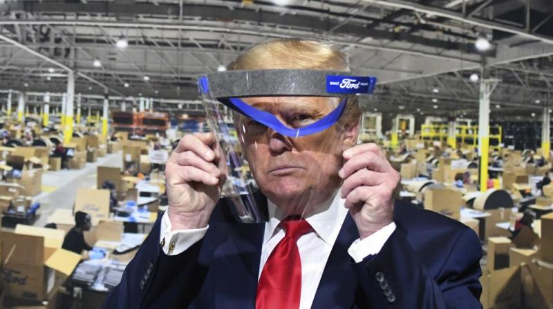 President Donald Trump looks through a face shield, in front of poster of the manufacturing of these shields, while touring Ford Motor Co.'s Rawsonville Components Plant in Ypsilanti, Michigan. (AP)