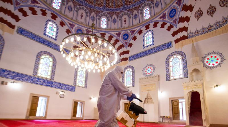 A worker sprays disinfectant inside the Banya Bashi Mosque in Sofia. (AFP)