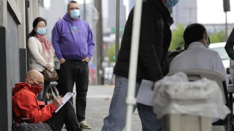 Pedestrian (lower left) fills out a job application, Saturday, May 16, 2020, during a walk- and drive-up job hiring fair in Seattle. (AP)