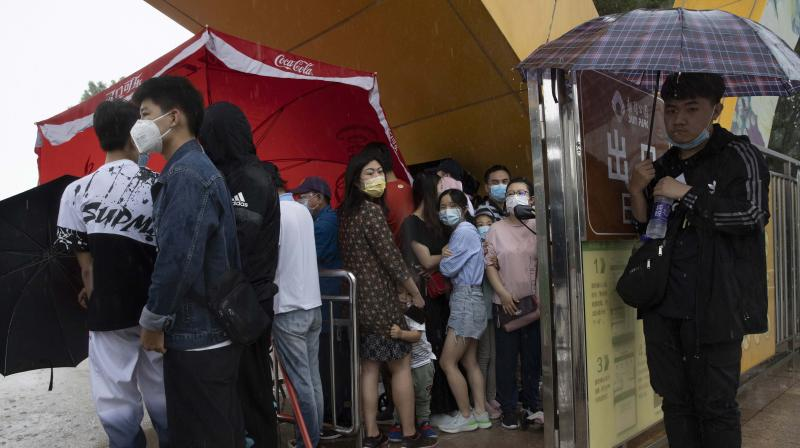 Visitors wearing mask to curb the spread of the coronavirus takes shelter from a sudden rainstorm in Beijing. (AP)
