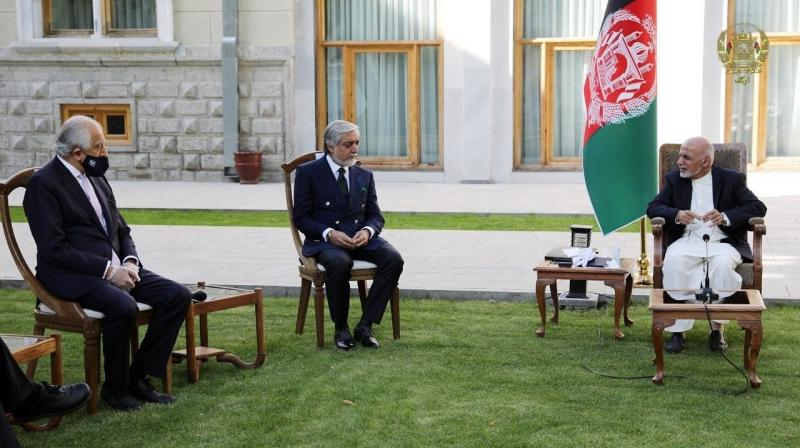 Afghan President Ashraf Ghani, right, and fellow leader under a recently signed power-sharing agreement, Abdullah Abdullah, center, hold a meeting with U.S. peace envoy Zalmay Khalilzad aimed at resuscitating a U.S.-Taliban peace deal signed in February, at the Presidential Palace, in Kabul, Afghanistan. (The Presidential Palace via AP)