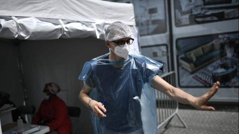 A health staff member instructs patients to stop as Seine-Saint-Denis French department inhabitants wait to be tested for the novel coronavirus Covid-19 at a free mobile testing site in Clichy-sous-Bois. (AFP)