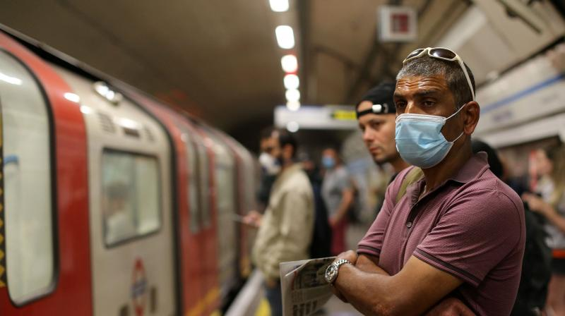 Commuters wear PPE (personal protective equipment), including a face mask as a precautionary measure against COVID-19. (AFP)