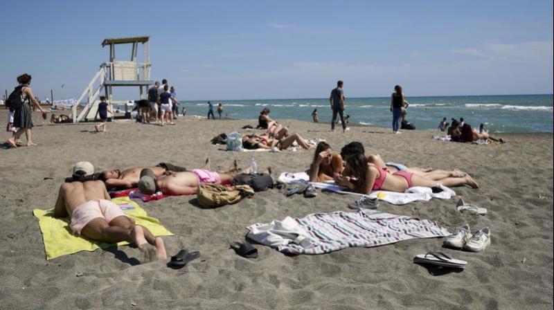 People sunbathe in Ostia beach, near Rome. (AP)