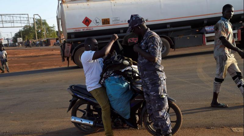 A policeman searches a vendor on a motorbike in Cinkasse, the northern Togo commercial border post with Burkina Faso. (AFP)