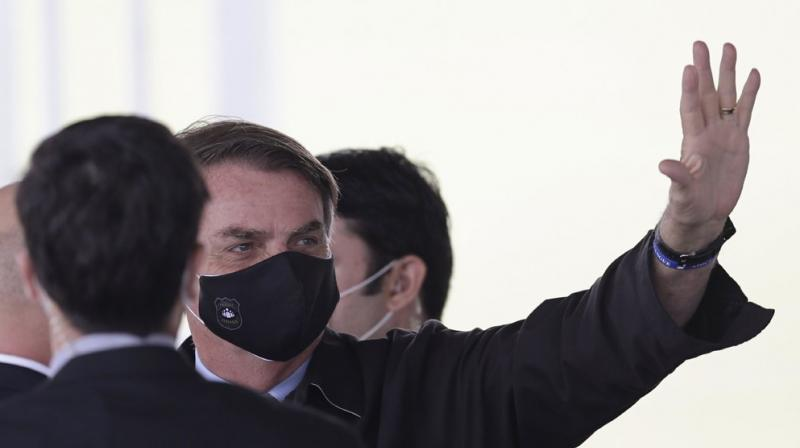 Brazil's President Jair Bolsonaro, wearing a face mask amid the new coronavirus pandemic, waves to supporters as he leaves the official residence of Alvorada palace, in Brasilia, Brazil. (AP)