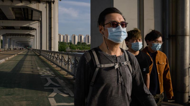 People wearing face masks amid concerns of the COVID-19 novel coronavirus walk along a bridge across the Han river in Seoul. (AFP)