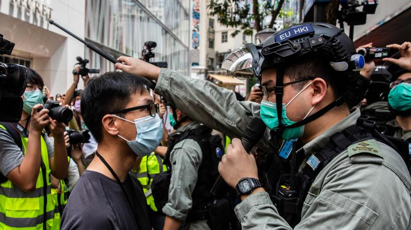 Police guard an MTR station exit near the Legislative Council in Hong Kong on May 27, 2020, ahead of a debate over a law that bans insulting China's national anthem. (AFP)