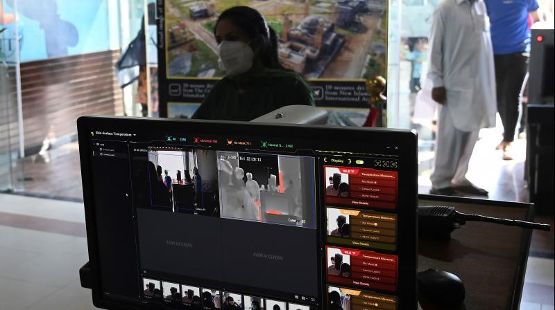 A shopping mall official (unseen) uses a thermal scanner to check the temperature of shoppers before they enter at the Centaurus Mall after the government eased a nationwide lockdown imposed as a preventive measure against the COVID-19 coronavirus, in Islamabad. (AFP)