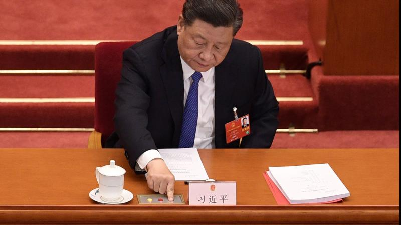 Chinese President Xi Jinping votes on a proposal to draft a security law on Hong Kong during the closing session of the National People's Congress at the Great Hall of the People in Beijing on May 28, 2020. (AFP)