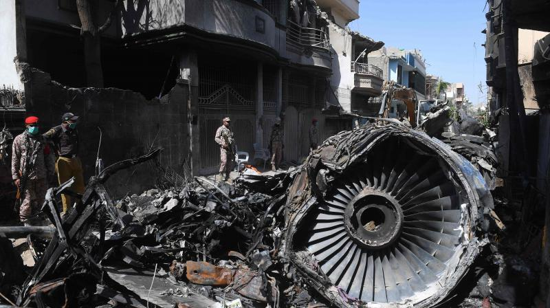 Security personnel stand beside the wreckage of a plane at the site after a Pakistan International Airlines aircraft crashed in a residential area in Karachi. (AFP)