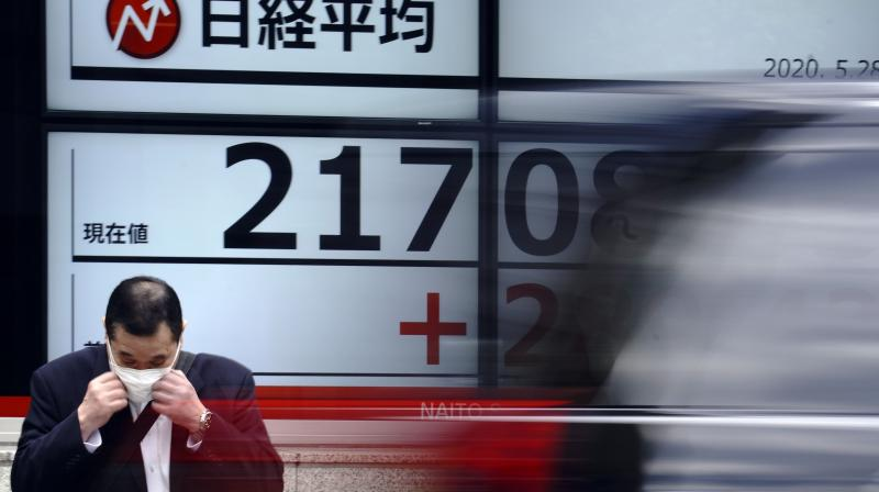A man adjusts a mask in front an electronic stock board showing Japan's Nikkei 225 index at a securities firm in Tokyo. (AP)