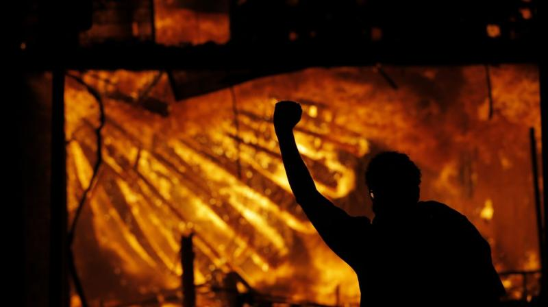 A protester gestures in front of the burning 3rd Precinct building of the Minneapolis Police Department on Thursday, May 28, 2020, in Minneapolis. (AP)
