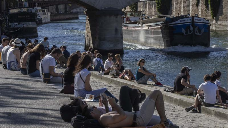 People stroll along the Seine river banks in Paris. (AP)