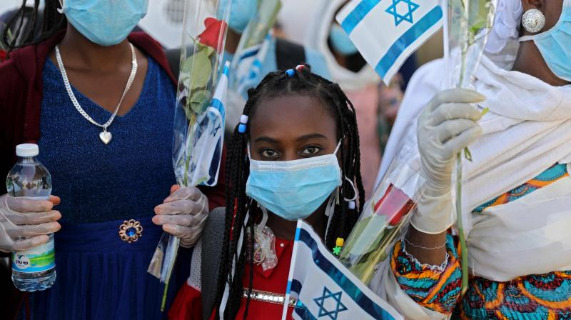 Ethiopian Jewish immigrants making their Aliyah (Immigration to Israel) in protective gear amid the COVID-19 pandemic, wave Israeli flags as they step off a plane at Ben Gurion International Airport in Lod, east of Tel Aviv. (AFP)