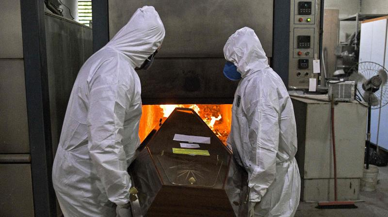 Crematorium workers wearing personal protective equipment as a preventive measure against the spread of the COVID-19 coronavirus pandemic, push a corpse into the oven of its crematorium at Sao Francisco Xavier cemetery, in Rio de Janeiro, Brazil. (AFP)