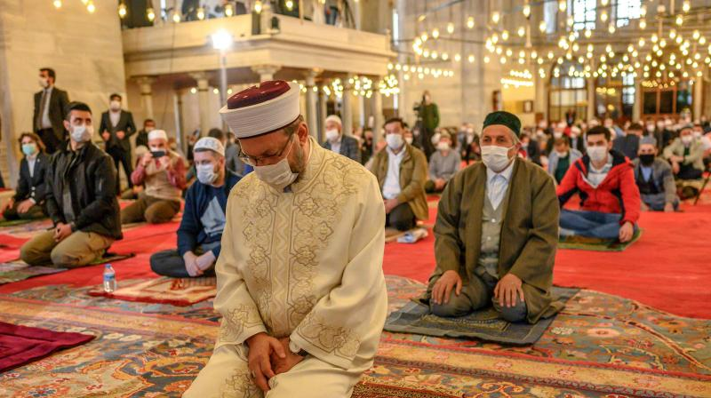 Ali Erbas, the head of Turkey's highest religious authority prays in front of worshippers wearing protective facemasks maintaining the required social distance during the Friday prayer in The Fatih Mosque in Istanbul. (AFP)