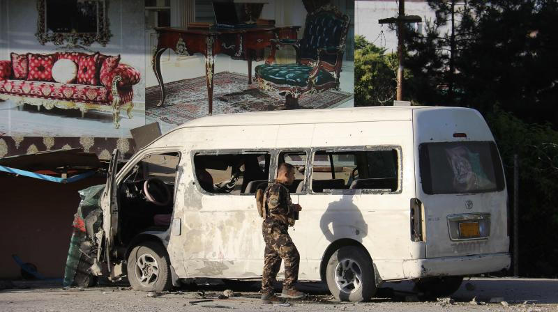 An Afghan security personnel investigates a damaged vehicle carrying employees of Khurshid TV along a roadside, at the site of a bomb blast in Kabul on May 30,2020. (AFP)