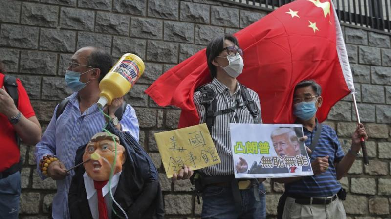 Pro-China supporters hold the effigy of U.S. President Donald Trump and Chinese national flag outside the U.S. Consulate during a protest, in Hong Kong, Saturday, May 30, 2020.(AP)