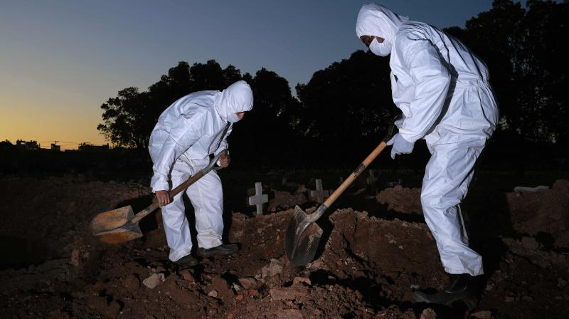 Cemetery workers wearing protective clothing bury a victim of COVID-19 at the Sao Franciso Xavier cemetery in Rio de Janeiro, Brazil. (AFP)