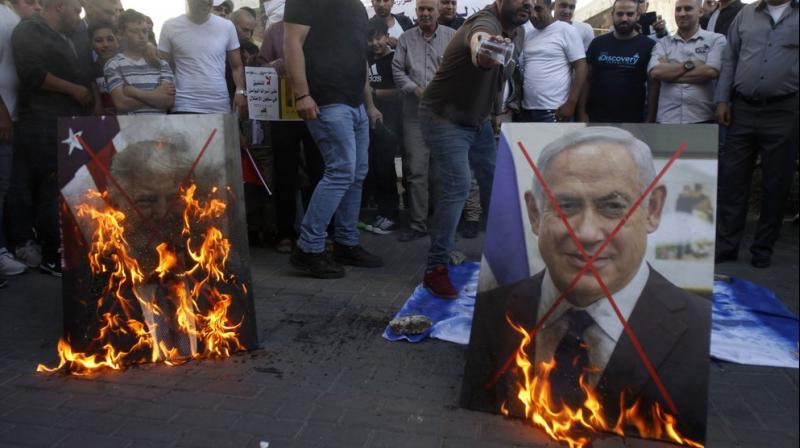 Palestinians burn pictures of U.S. President Donald Trump, left, and Israeli Prime Minister Benjamin Netanyahu during a protest against Trump's mideast initiative, in the West Bank city of Nablus. (AP)