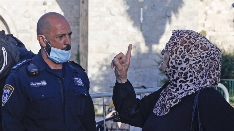 A Palestinian woman argues with a member of Israeli security forces, as she takes part in a protest at the Damascus Gate of the old city of Jerusalem. (AFP)