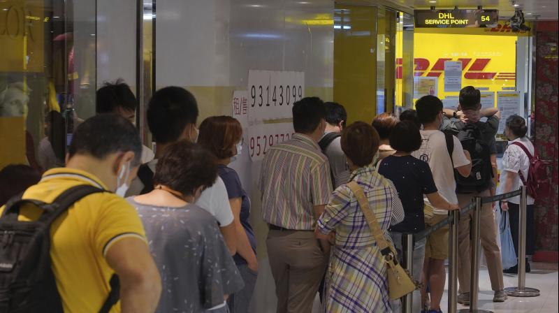 People lined up at DHL courier outlets across the city, many to send documents to the U.K. to apply for or renew what is known as a British National (Overseas) passport. (AP)