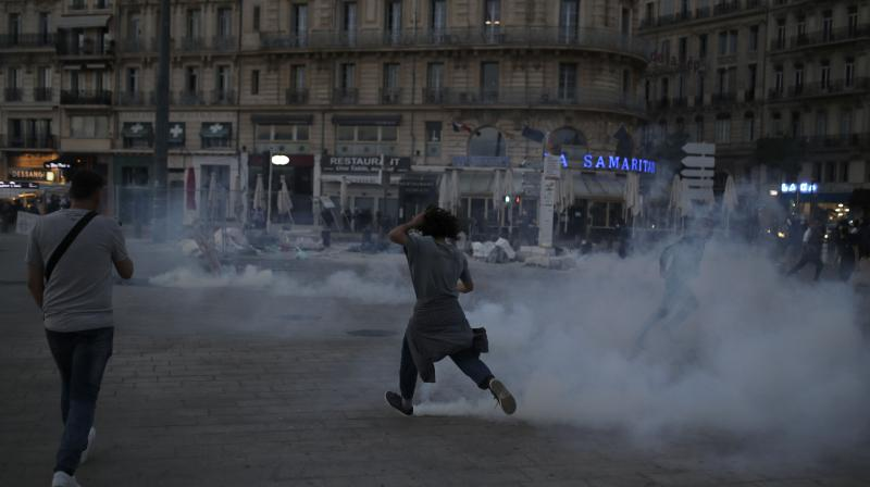 A protester runs among tear gas during a demonstration Tuesday, June 2, 2020 in Marseille, southern France. (AP)