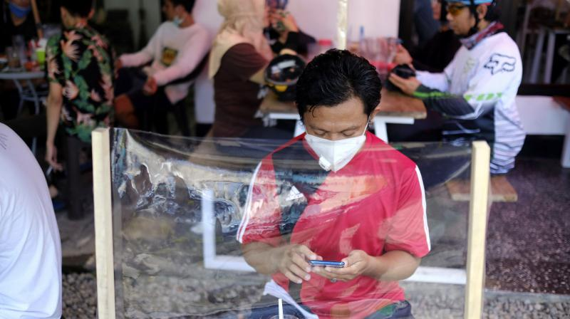 A man checks his mobile phone at a coffee shop, sitting in front of a plastic sheet barrier installed to help curb the new coronavirus outbreak in Indonesia. (AP)
