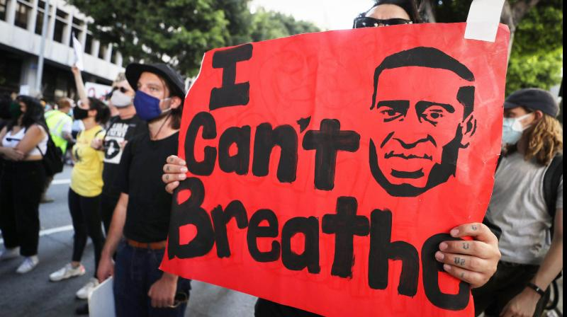 A protester holds a sign reading 'I Can't Breathe' outside the District Attorney's office during a peaceful demonstration over George Floyds death. (AFP)